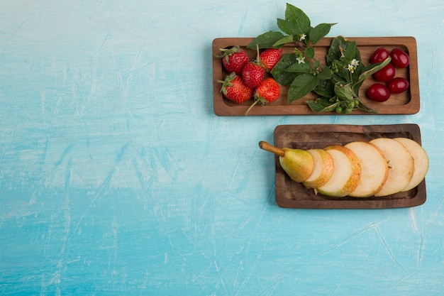 Sliced pears with strawberries in wooden platters, top view