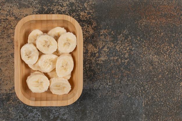 Banane sbucciate a fette sul piatto di legno.