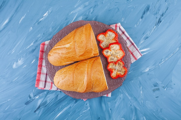 Нарезанный перец и хлеб на доске на кухонном полотенце, на синем столе.