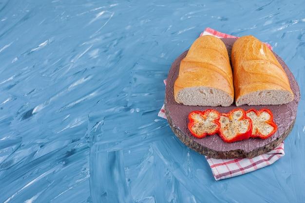 Нарезанный перец и хлеб на доске, на кухонном полотенце, на синем.