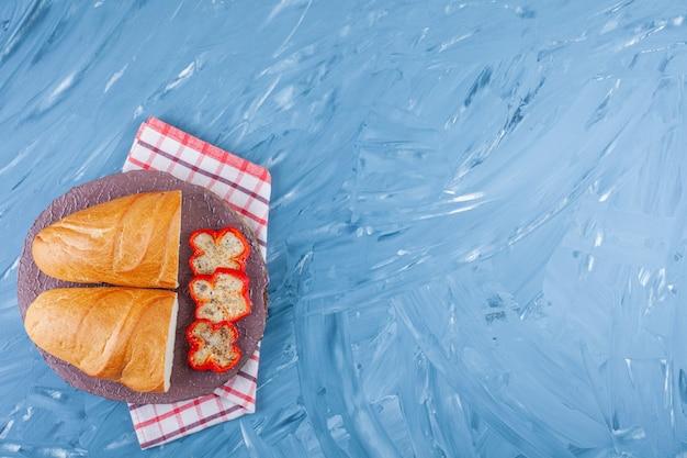 Нарезанный перец и хлеб на кухонном полотенце на синем.