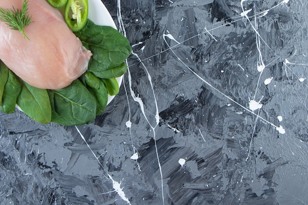 대리석 배경에 접시에 고추, 시금치, 닭 가슴살을 슬라이스.
