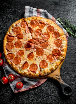 Sliced pepperoni pizza with rosemary and tomatoes.