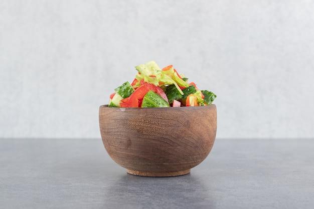 Peperoni a fette, cetrioli e semi di melograno in ciotola di legno. foto di alta qualità