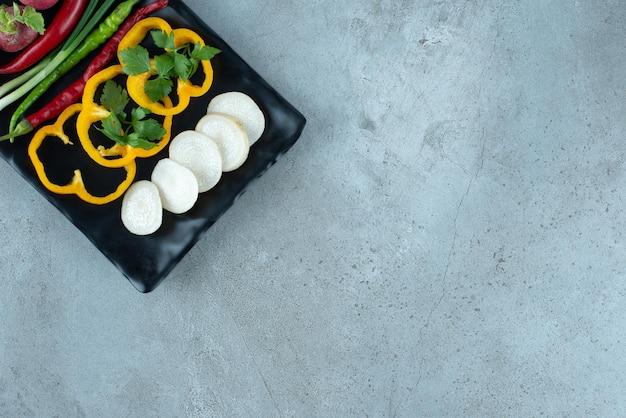 검은 접시에 얇게 썬 고추, 채소, 양파.