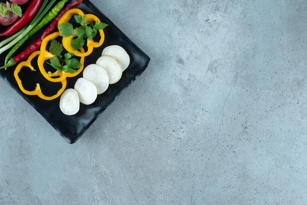 Peperoni, verdure e cipolle affettate sulla banda nera.