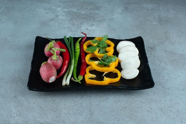 검은 접시에 얇게 썬 고추, 순무, 채소, 양파.