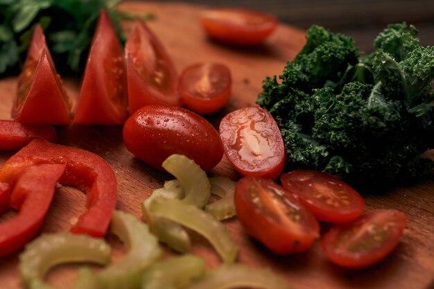 Нарезанные соленья и помидоры на деревянной кухонной доске
