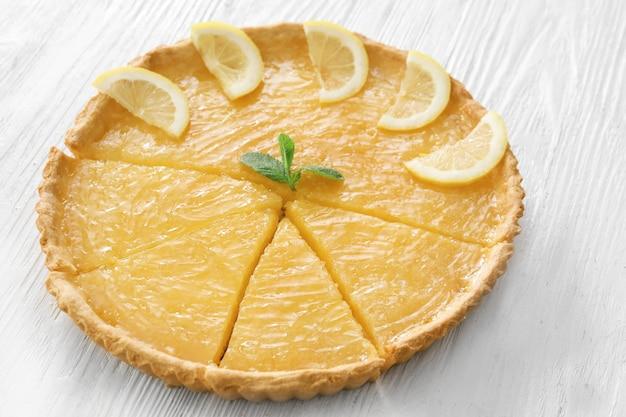 나무 테이블에 레몬과 민트로 장식 된 파이 슬라이스