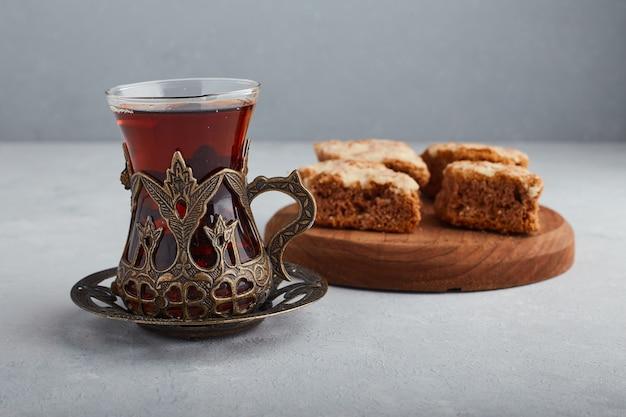 Нарезанный пирог на деревянном блюде с стаканом чая.