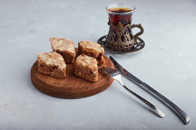 Sliced pie on a wooden platter with a glass of tea on white surface.
