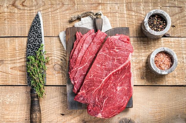 나무 커팅 보드에 대리석 생 쇠고기 고기 조각. 나무 배경입니다. 평면도.
