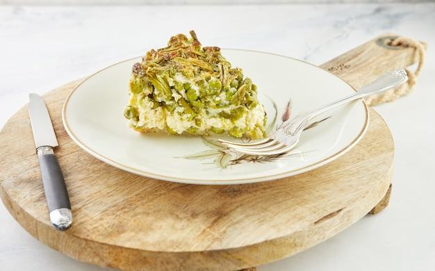 プレートと木製のスタンドにアスパラガスとエンドウ豆をスライスしたパイ。ステップバイステップのレシピ。