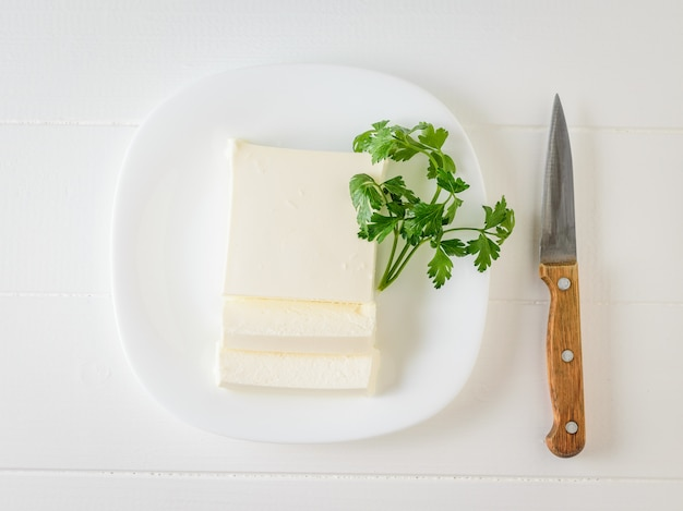 Sliced piece of serbian cheese with parsley on a plate on a white table.