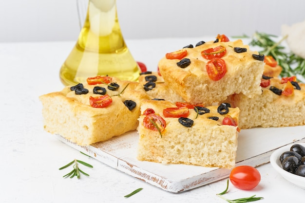 Sliced pieces of focaccia with tomatoes, olives and rosemary. copy space for text.