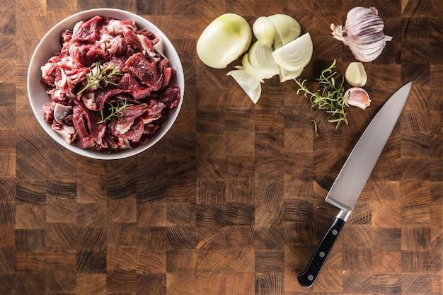로즈마리 양파와 마늘을 곁들인 접시에 얇게 썬 쇠고기 조각.