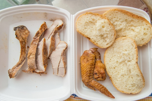 Кусочки холодной запеченной свинины в пластиковом контейнере, с кусочками пшеничного хлеба и жареным куриным крылышком, аппетитная закуска.