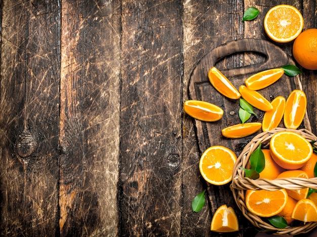 木製の背景のバスケットにオレンジのスライス