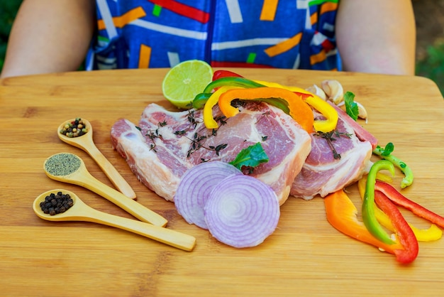 木の表面にバーベキュー用の生肉をスライスしたもの、メニューの料理レシピ。食品、生ステーキ、ビーフステーキバーベキュー、トマト、ピーマン、肉を調理するためのスパイス。