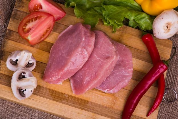 新鮮な野菜のトマト、木製の表面にレタスとバーベキュー用の生肉のスライス部分。上面図。