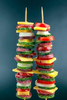 Нарезанные кусочки колбасы, салями, сыра, огурца и помидора