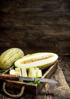 Sliced pieces of ripe melon on an old tray on a wooden background