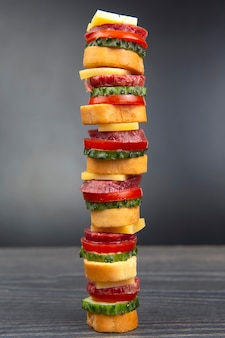 Sliced pieces of sausage, salami, cheese, cucumber and tomato. fast food. ingredients for pizza. calories and diet