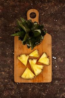 スライスしたパイナップル、茶色の机と素朴な床で熟したジューシーで熟した上面図