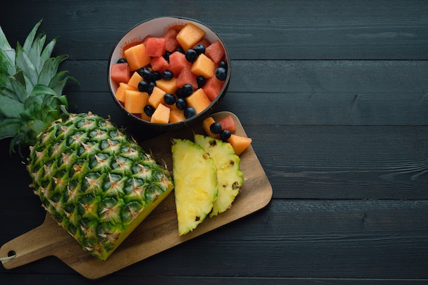 Sliced pineapple and bowl of fruits on black wooden background. top view.