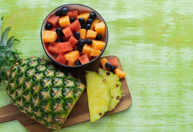 Sliced pineapple and bowl of fruits on green wooden background