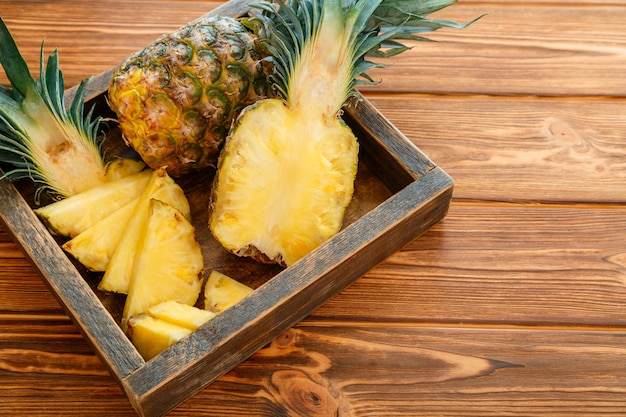 スライスしたパイナップル。ブロメライントロピカルサマーフルーツパイナップルの半分と全体のパイナップルは、コピースペースのある木製の箱の茶色の暗いテーブルにあります。高品質のストックフォト