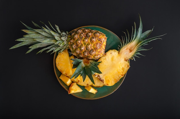 Sliced pineapple. bromelain whole pineapple tropical summer fruit halves pineapple black dark background on green plate. summer fruit dessert top view. high quality stock photo