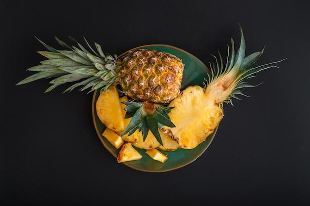 スライスしたパイナップル。ブロメライン全体のパイナップル熱帯夏の果物は、緑のプレートにパイナップルの黒い暗い背景を半分にします。夏のフルーツデザート上面図。高品質のストックフォト