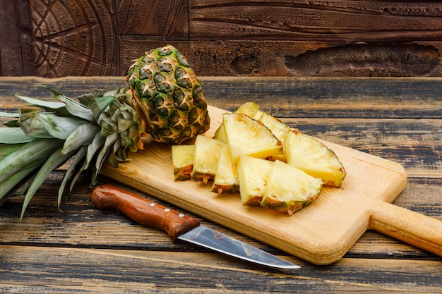 Sliced pineapple in a cutting board with a fruit knife side view on a wood grunge surface and stone tile
