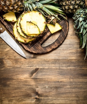 Sliced pineapple on cutting board with a knife on wooden table.