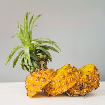 Sliced pineapple in front of grey wall