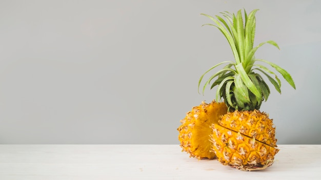 Sliced pineapple fruit in front of grey wall