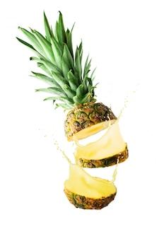 Нарезанный ананас на белом фоне с брызгами сока