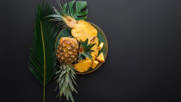 熱帯のヤシの葉で皿にパイナップルをスライスしました。ブロメライン全体のパイナップル夏の果物は、黒い暗い背景にパイナップルを半分にします。夏のフルーツデザート。長いウェブバナー上面図コピースペース