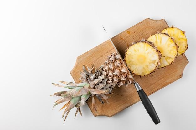 Ломтики ананаса с ножом на кухонной доске