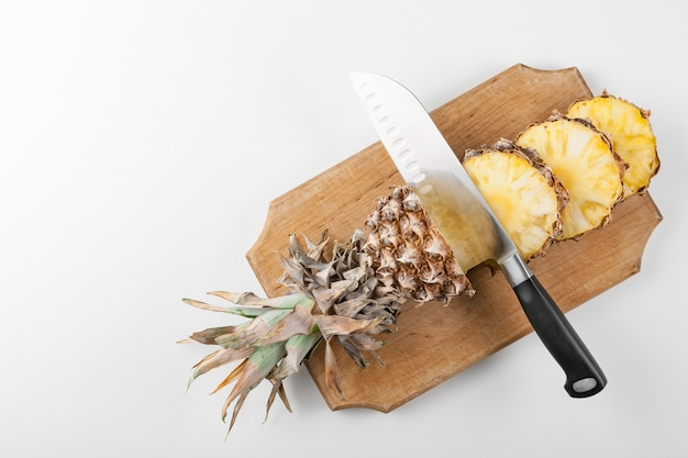 Sliced pineapple slices with a knife on a kitchen board