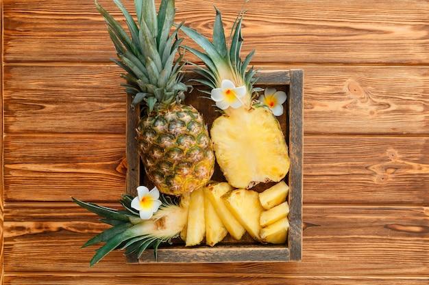 얇게 썬 파인애플 열대 여름 과일 파인애플 반쪽과 전체 파인애플을 짙은 갈색 테이블에 얹은 ...