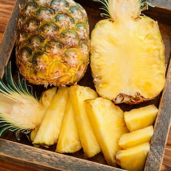 Sliced pineapple. tropical summer fruit pineapple halves and whole pineapple on brown dark table in wooden box with tropical plumeria flowers. bromelain close up. high quality stock photo