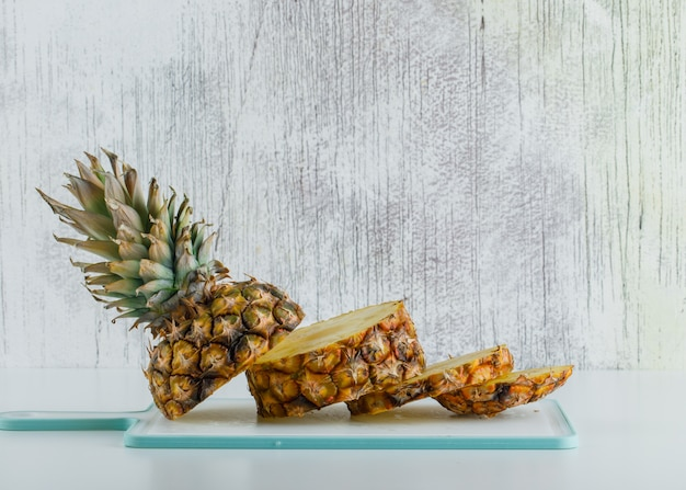 Sliced pineapple with cutting board