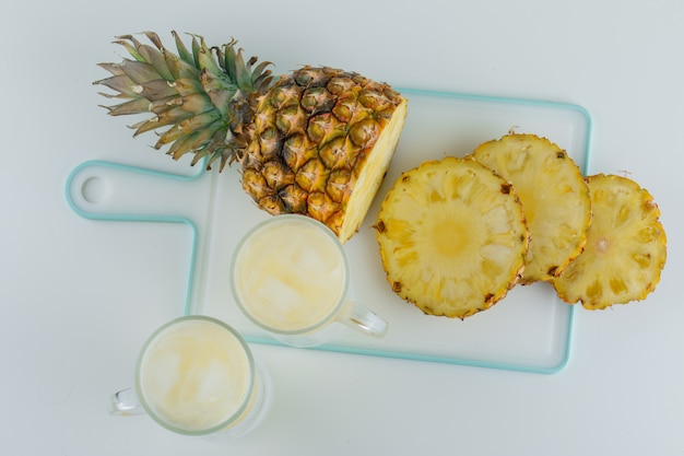Sliced pineapple with juice on white and cutting board surface