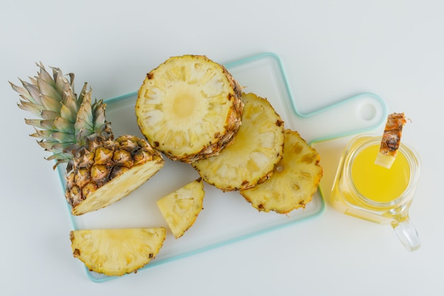 Sliced pineapple with juice on white and cutting board