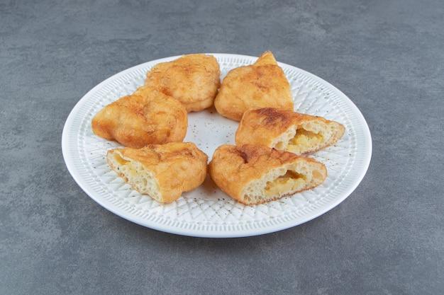 Piroshki affettato con patate sul piatto bianco.