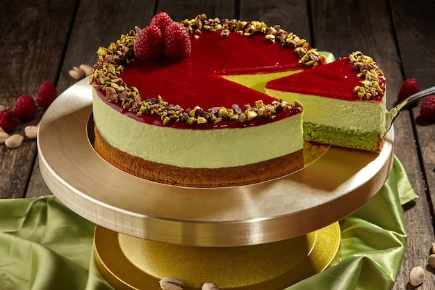 Sliced pistachio cheesecake with raspberry jelly on cake stand