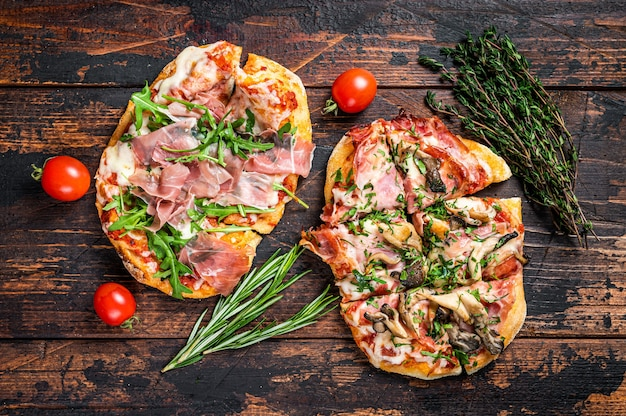 Sliced pizza with prosciutto parma ham, arugula and parmesan cheese. dark wooden background. top view.