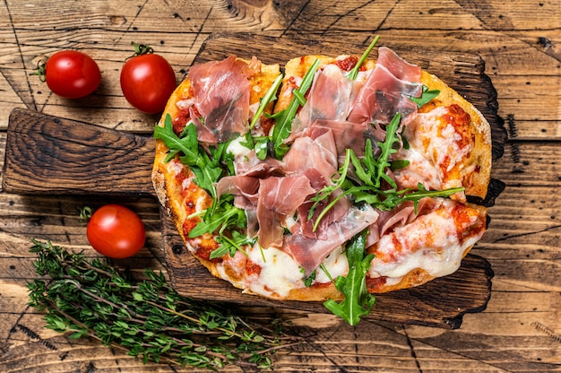 Sliced pizza with prosciutto parma ham, arugula and parmesan cheese on a wooden board. wooden background. top view.